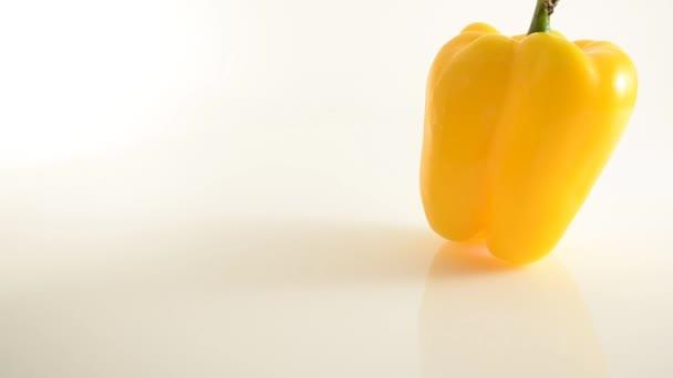 Rotation von gelbem Pfeffer auf Acryl gegen Weiß - Kran auf