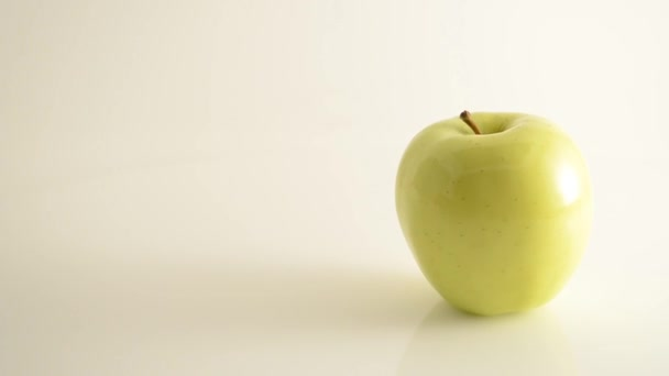 Rotating Golden Delicious Apple On Acrylic Against White - Crane Down
