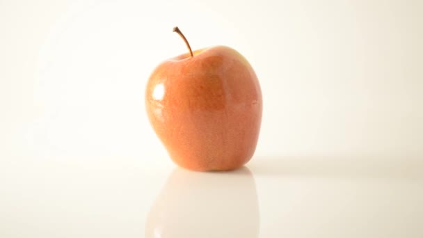 rotierender Sonya-Apfel auf Acryl gegen Weiß - Stempel links