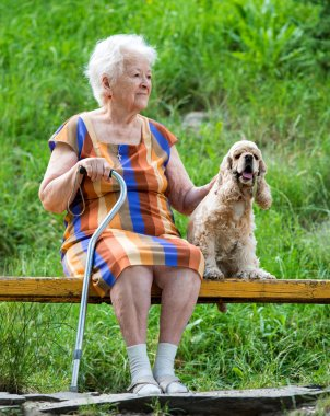 Old woman and her dog sitting on a bench