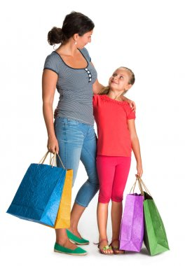 Smiling mother and daughter with shopping bags