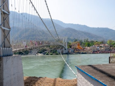 Bridge Laxman Jhula with Pedestrians, on the Holy Ganges river flows through Rishikesh (world capital of Yoga) - holy city for the Hindus stock vector