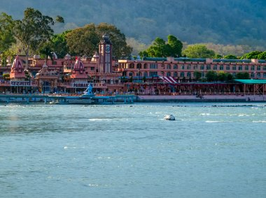 Panorama view of the Holy Ganges river that flows through Rishikesh (the world capital of Yoga) - the holy city for the Hindus, India. stock vector