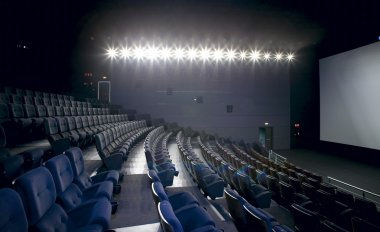 Cinema interior with lights on. Chairs and screen.
