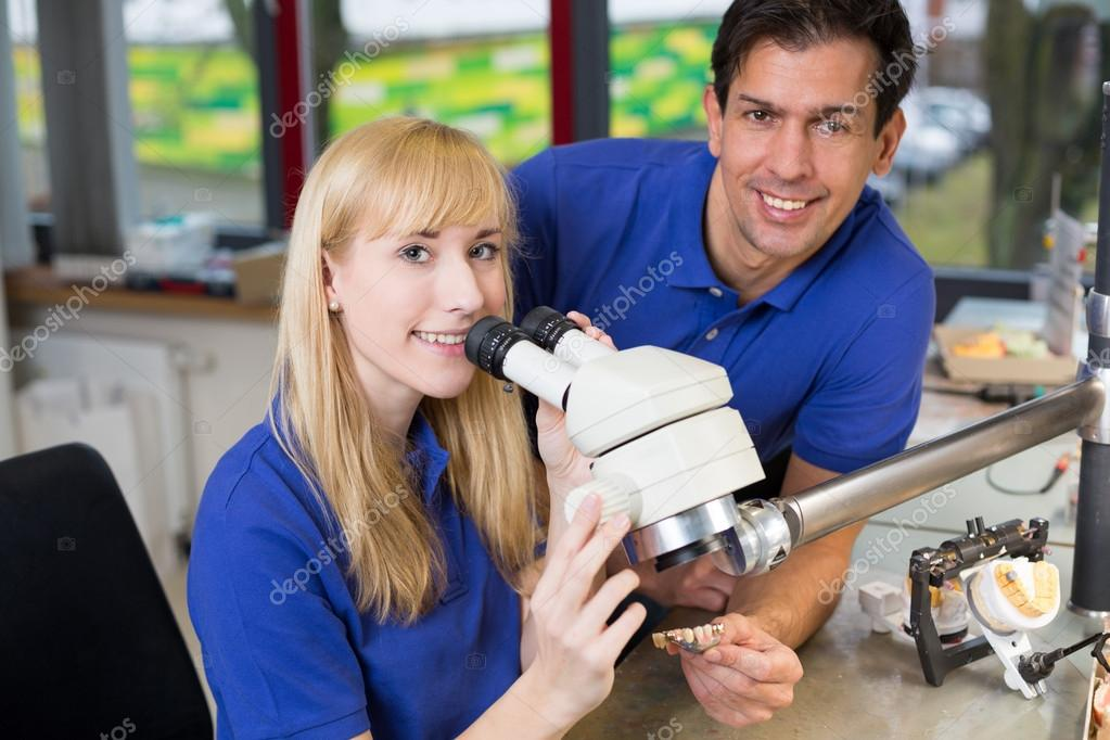 Apprentice and dental technician at microscope