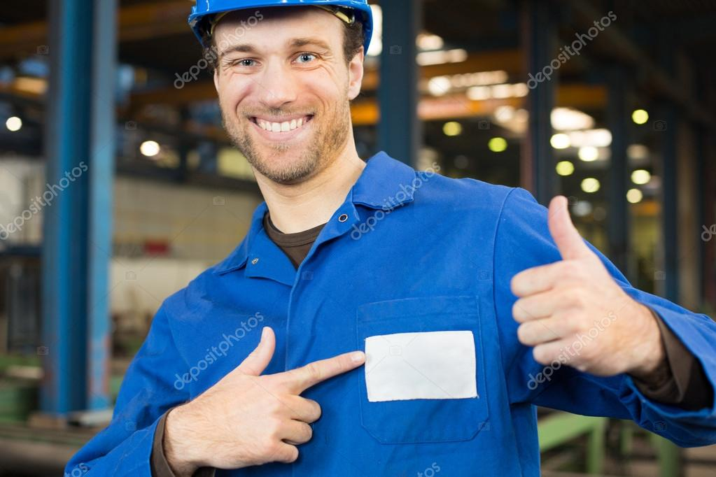 Construction worker with helmet in assembly hall with thumbs up