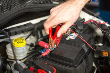 Car mechanic changing the battery