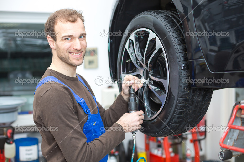 Mechanic wielen op een auto op hydraulische helling wijzigen