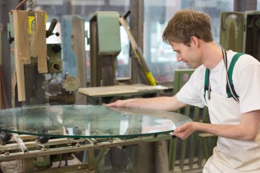 Glazier grinding a pieco of glass