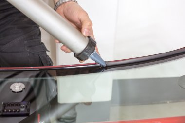Glazier applying rubber sealing to windscreen