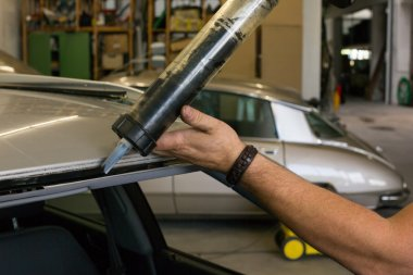 Glazier using application gun to apply adhesive for windscreen