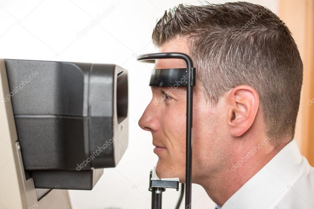 Patient and auto refractometer at optician or optometrist