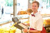 Cashier (Pokladna) v pekařství pózuje s pokladnou