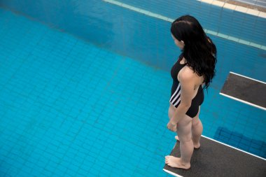 Woman on spring board at public swimming pool