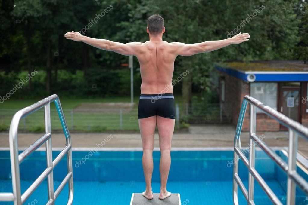 Hombre listo para saltar del trampol n en la piscina for Trampolin para piscina
