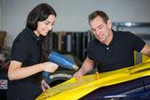Fotografie Car wrappers using heat gun to prepare vinyl foil