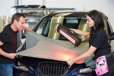 Car wrappers using red light lamp to flatten vinyl film