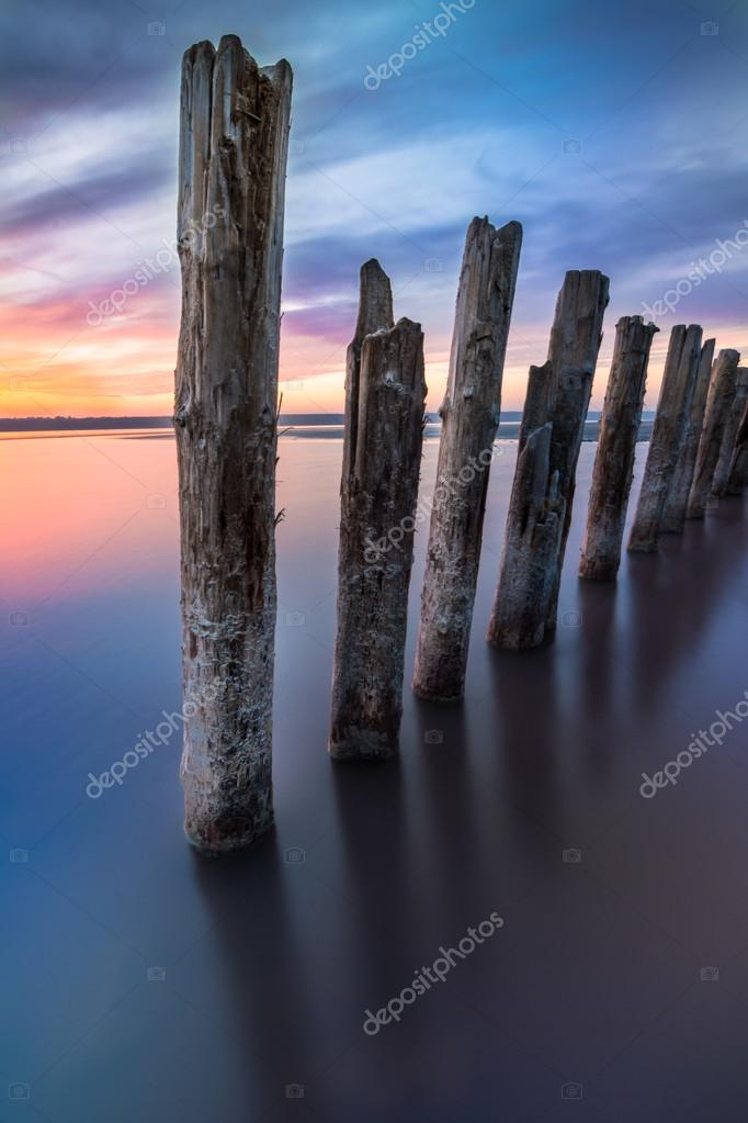 Unusual pillars in the water on the background of colorful sky