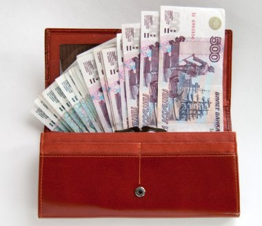 Orange leather wallet full of one hundred roubles