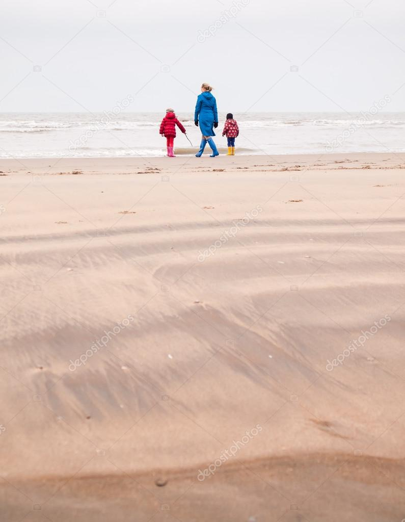 01582fe6eb Woman with small boy and girl in winter clothing and rubber boots on a winter  beach looking out to sea — Photo by ...