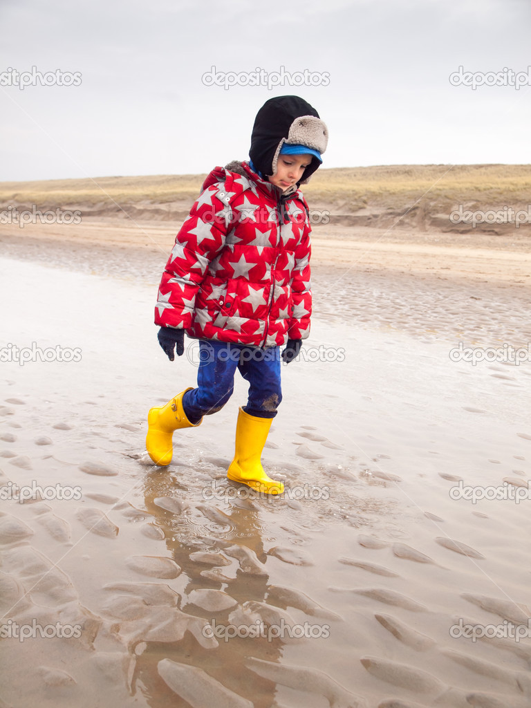 fbdc980cba Small boy in winter clothing and rubber boots paddling in a tide pool on a winter  beach — Photo by ...