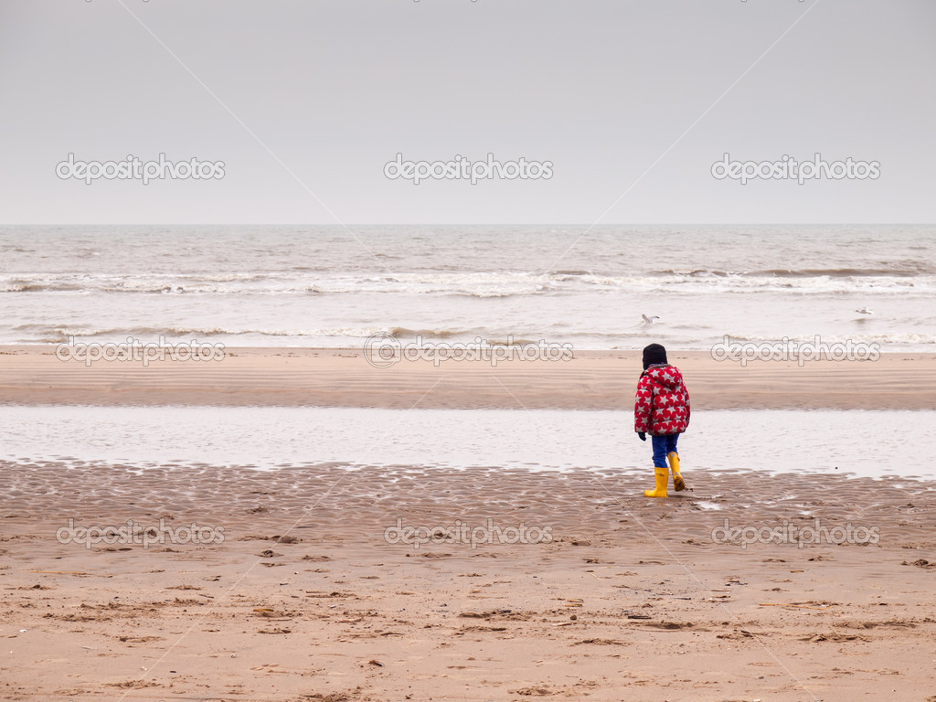 81eb6d52ef Small boy in winter clothing and rubber boots on a winter beach — Photo by  davidhanlon