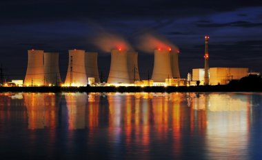 Nuclear power plant by night with reflection