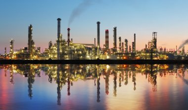 Oil and gas refinery at twilight with reflection