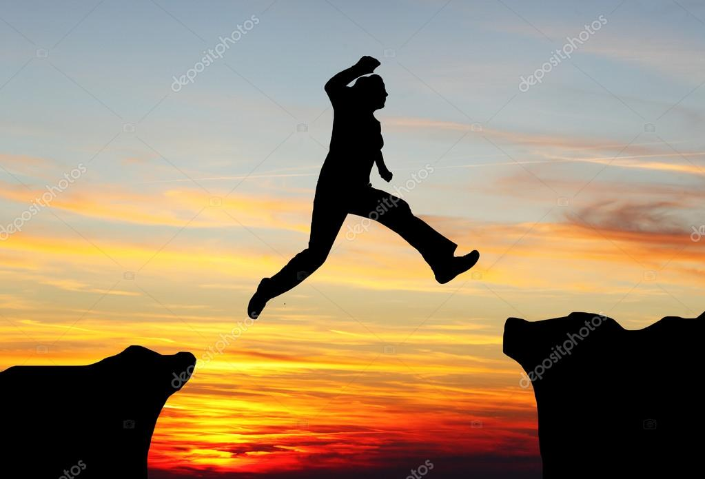 Silhouette of man jumping over the mountains