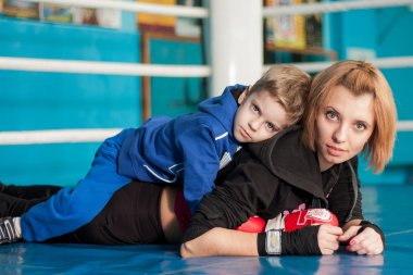 Mother teaches son of boxing in the gym.