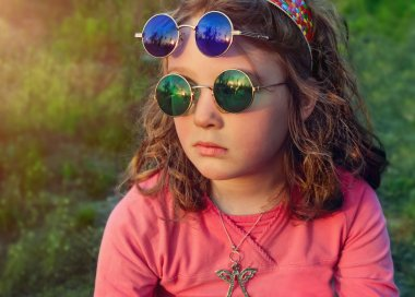 Little girl in two pairs round colored glasses