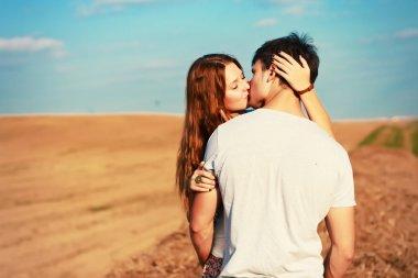 couple kissing in field.