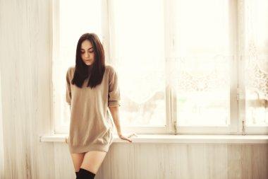 Young pretty woman near the window.