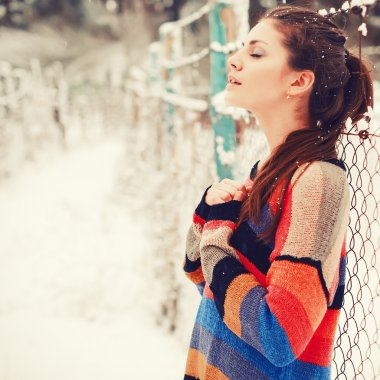 Beautiful brunette in winter with closed eyes.
