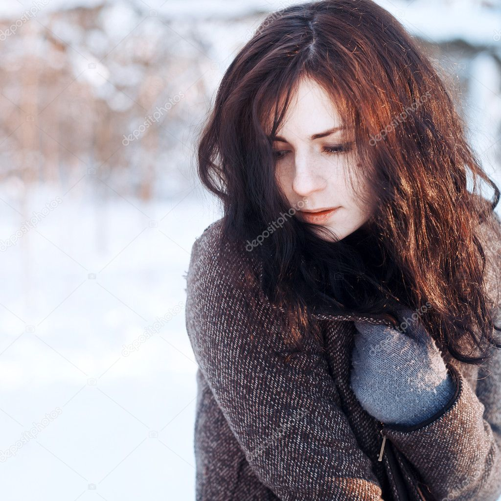 Young brunette in winter park.