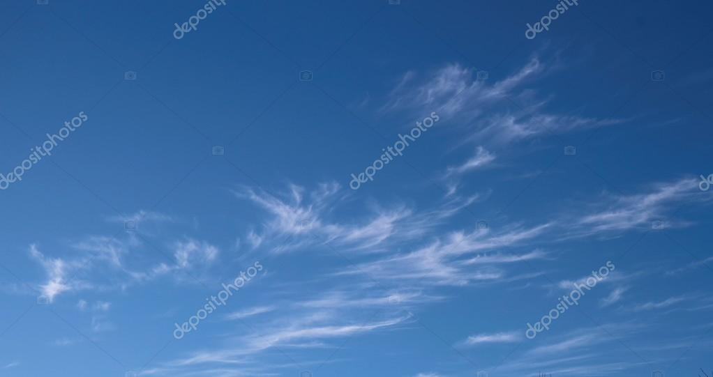 A horizontal shot of bright blue sky with puffy white clouds.