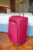 Photo Red suitcase stands up inside a hotel room