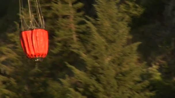 Hasičské vrtulník sbírá vodu z řeky