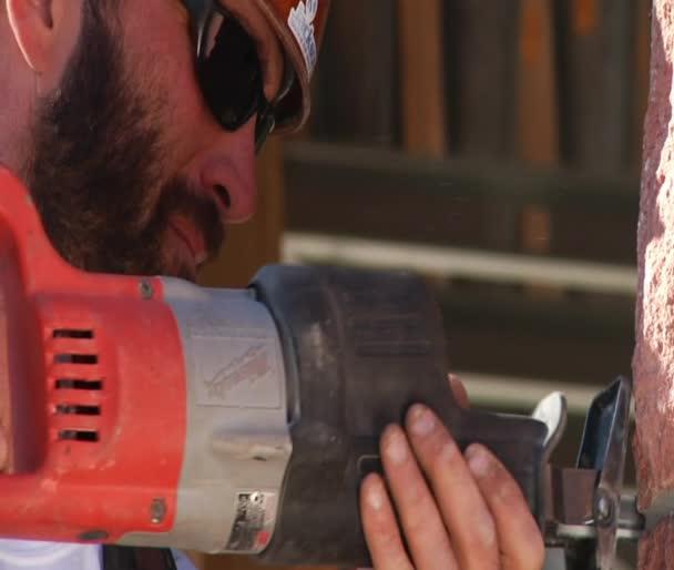 Bauarbeiter setzt Elektrowerkzeug ein