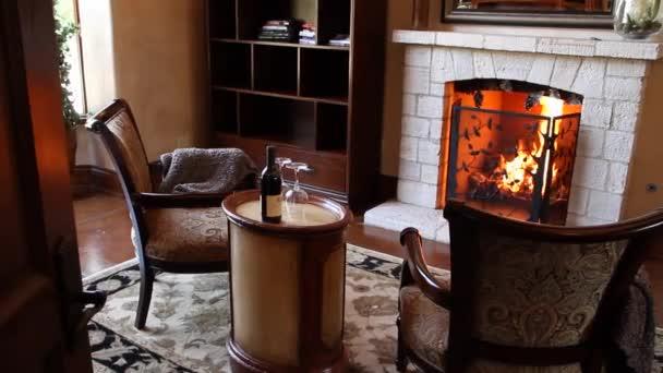 útulné židle před krb s lahví vína