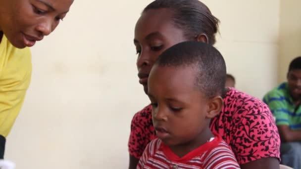 dítě čeká očkování na haiti