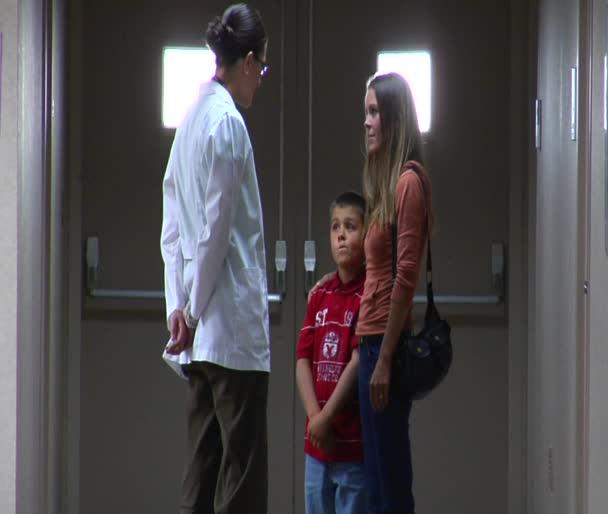 Doktor mluví s matkou a synem v chodbě