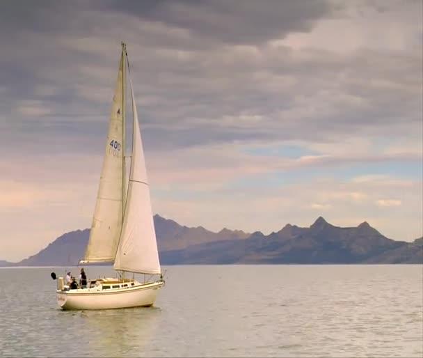 plachetnice klouže na klidné vodě poblíž hory