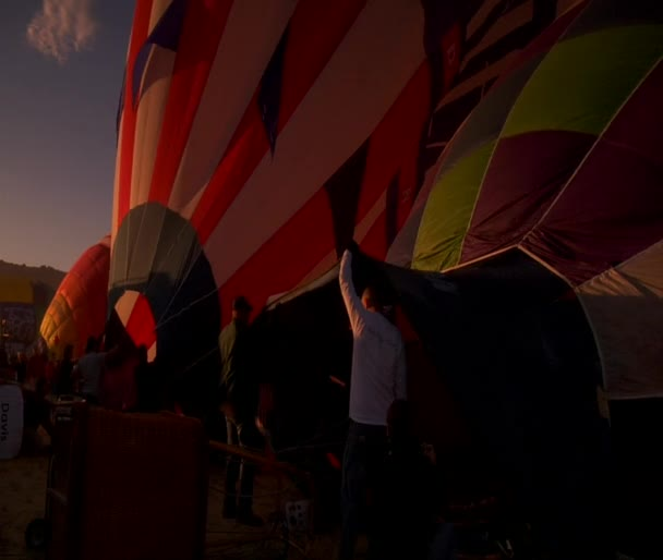 Partially filled hot air balloons languish on the ground