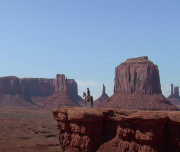 Kovboj a jeho kůň stojí na útesu v Monument Valley