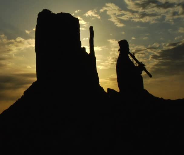rodilý Američan hraje flétna s monument valley sunrise