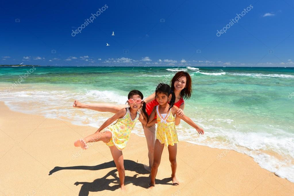 Mother and children playing at the beach
