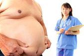 Fotografie vážné lékař zkoumá pacienta obezity