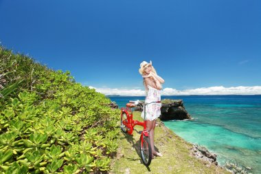 Woman with a bike by the ocean