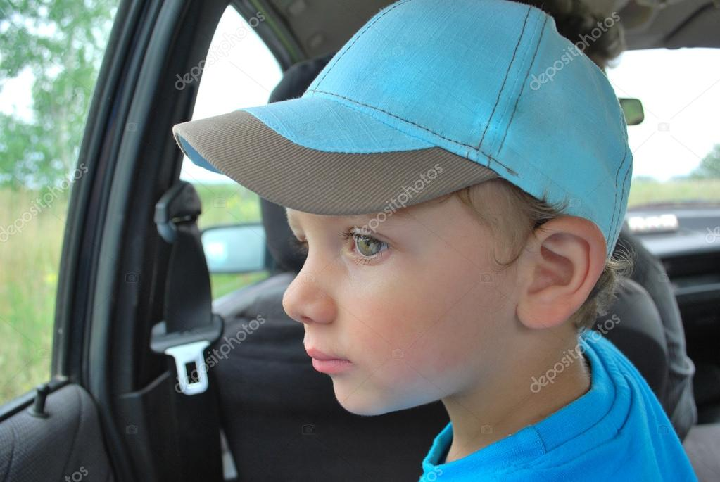 the little boy sitting in a car looking out the window.